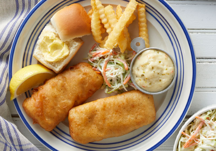 Link to story: Fish Fries: Five Midwestern Meal Must Haves. A Midwestern fish fry including, Cod, buttered dinner roll, crinkle cut fries, tartar sauce and coleslaw.