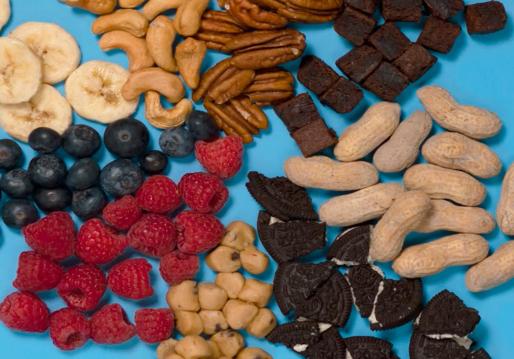 Link to story: Flavor of the Day: The Anatomy of Flavor. Toppings and mix-ins: bananas, blueberries, raspberries, cookie dough, Oreos, brownie pieces, peanuts, cashews and pecans radiating outwards in a circle