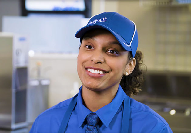 Brianna in her True Blue Crew uniform and smiling in a Culver's restaurant.