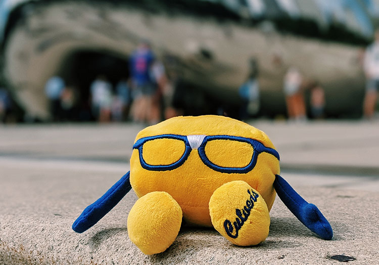 Link to story: Life with Curdis. Curdis mascot sitting on the pavement sitting in front of the Cloud Gate in Chicago