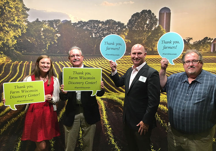 Four people, including Culver's CEO Joe Koss, pose for a photo in front of a farm backdrop at the Farm Wisconsin Discovery Center.