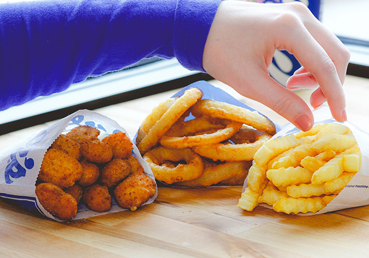 A hand reaches for Onion Rings, Crinkle Cut Fries and Cheese Curds on a table. Click here to take a food quiz: Can we guess which side you're craving?
