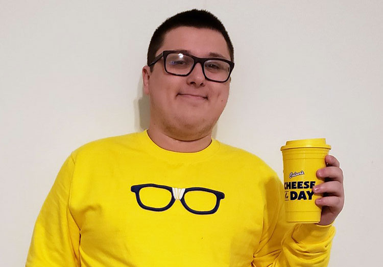 "Image of Kurtis Culver wearing a yellow Curd Nerd sweatshirt with black framed glasses, and holing a ""Cheese the Day"" yellow travel mug"