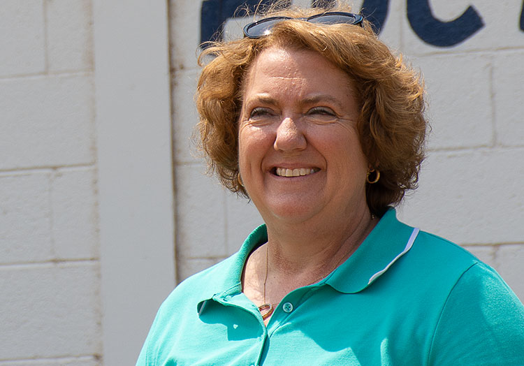 NCBA President Jennifer Houston poses in front of a livestock barn.