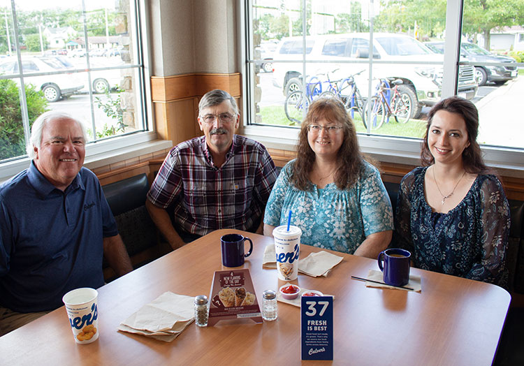 Link to story: Our very first guest. Craig Culver enjoys a meal in a corner booth with first guest Jim Olson, Jim's wife Marion and their daughter Heather.