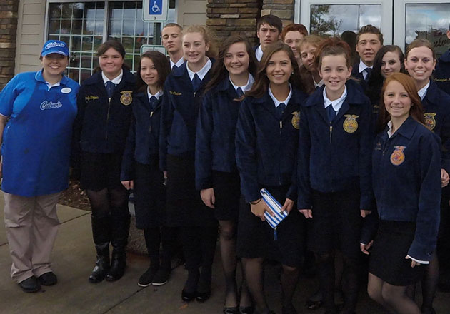 A group of FFA members stand with two Culver's team members outside a Culver's restaurant.