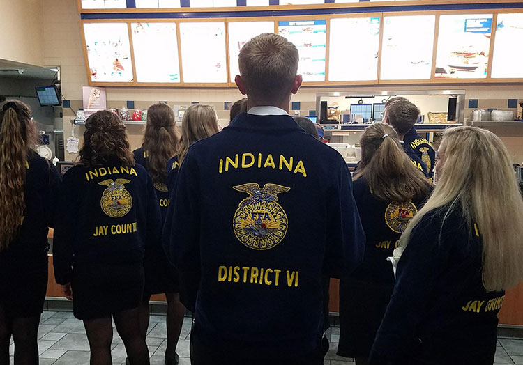 Link to story: Meet Culver's Team Members active in FFA. Photo of FFA members in their blue jackets stand in a Culver's restaurant looking at the menu board.