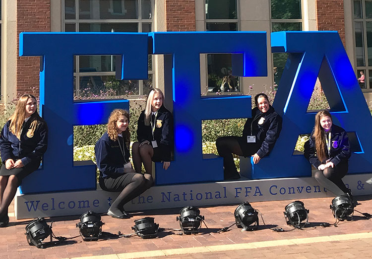 Five FFA Members in blue jackets pose along with a giant FFA sign