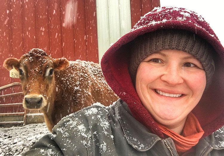 Marie takes a selfie with a cow on a snowy day.
