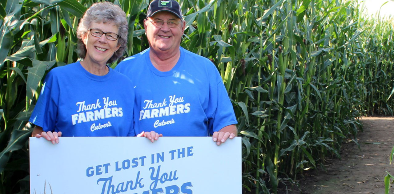 Iowa farmers Dave and Helen Huitink pose in front of their Thank You Farmers corn maze.