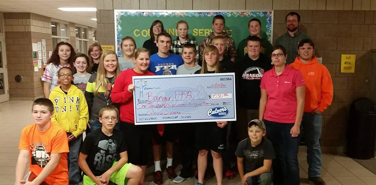 Large FFA Chapter poses in school with large check from Culver's