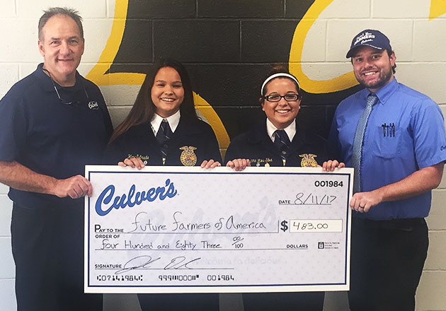 Peoria FFA members Hana Estrada and Aryanna Rios-Silva accept a donation check from Culver's owner Rob Bullock and general manager Joel Daniel.